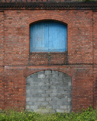 Old Brick Building With Covered Up Window Buildings
